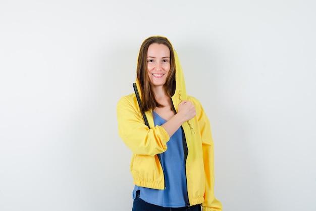 Młoda dama trzyma zaciśniętą pięść na klatce piersiowej w koszulce, kurtce i wygląda na pewną siebie