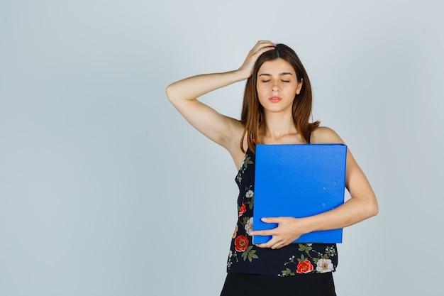 Młoda dama trzymając folder trzymając rękę na głowie w bluzce, spódnicy i patrząc na zmęczonego, widok z przodu.