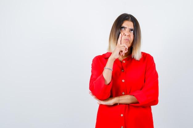 Młoda dama trzymając palec na policzku w czerwonej koszuli oversize i patrząc zamyślony. przedni widok.