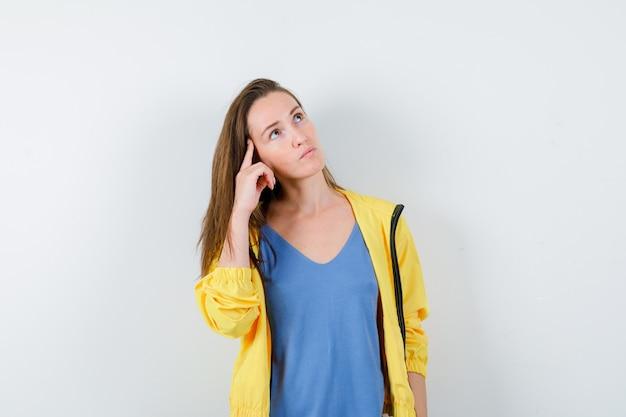 Młoda dama trzymając palec na skroniach w koszulce, kurtce i patrząc zamyślony. przedni widok.
