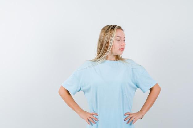 Młoda dama trzymając ręce w talii w t-shirt i wyglądająca pewnie, widok z przodu.