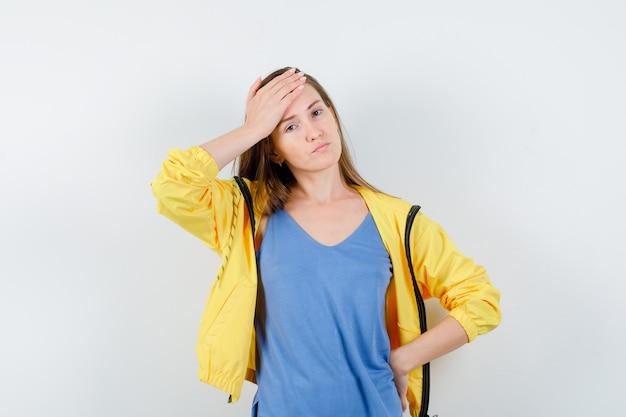 Młoda dama trzymając rękę na czole w koszulce, kurtce i patrząc zamyślony, widok z przodu.