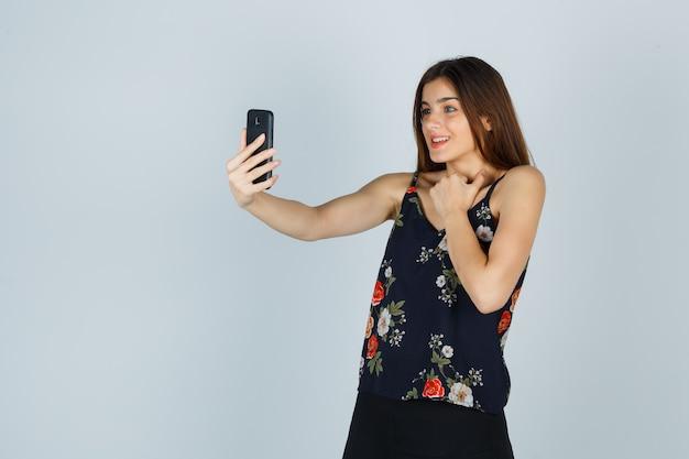 Młoda dama trzymając rękę na klatce piersiowej podczas wideorozmowy w bluzce i patrząc wesoło. przedni widok.