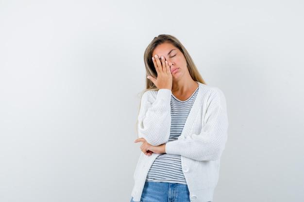 Młoda dama trzymając rękę na oku w koszulce, kurtce i patrząc na zmęczoną. przedni widok.