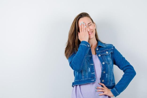 Młoda dama trzymając rękę na oku w t-shirt, kurtkę i wesoło. przedni widok.