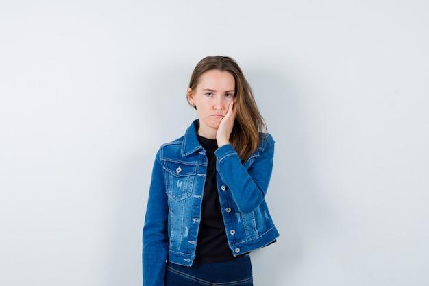 Młoda dama trzymając rękę na policzku w bluzce i patrząc smutny, widok z przodu.