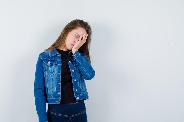 Młoda dama trzymając rękę na twarzy w bluzce i patrząc rozczarowany. przedni widok.