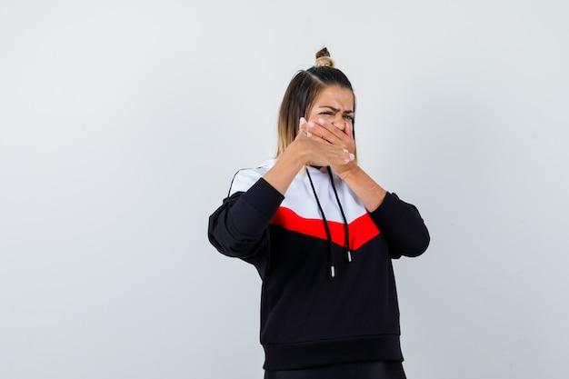 Młoda dama trzymając rękę na ustach, pokazując gest zatrzymania w swetrze z kapturem i patrząc zniesmaczony.