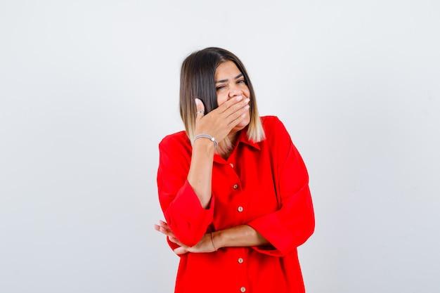 Młoda dama trzymając rękę na ustach w czerwonej koszuli oversize i patrząc zawstydzony, widok z przodu.