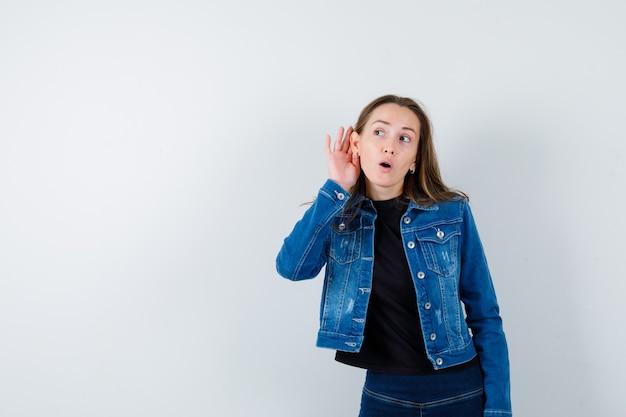 Młoda dama trzymając rękę za uchem w bluzce i patrząc ciekawy.