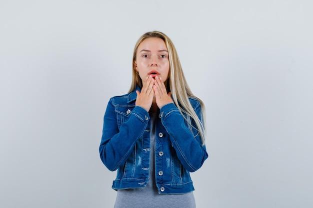 Młoda dama trzymając się za ręce na brodzie w t-shirt, kurtka dżinsowa, spódnica i patrząc zamyślony.