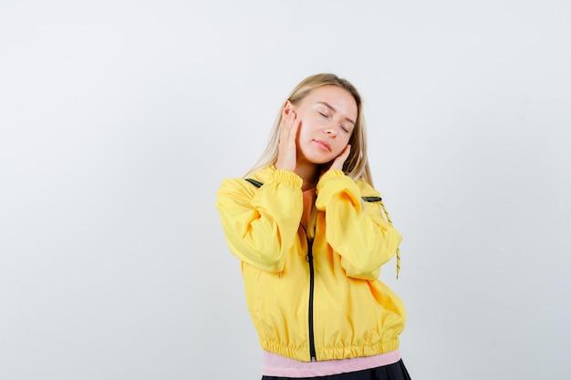 Młoda dama trzymając się za ręce na policzkach w koszulce, kurtce i patrząc śpiący