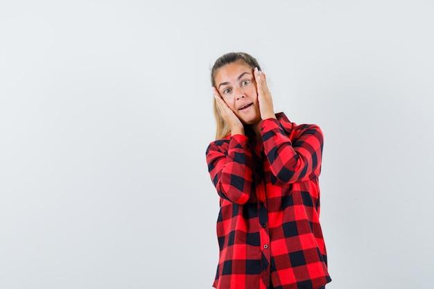 Młoda dama trzymając się za ręce na policzkach w swobodnej koszuli i wyglądająca pięknie. przedni widok.