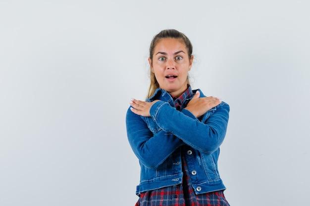Młoda dama trzymając się za ręce na ramionach w koszuli, kurtce i pięknie wyglądającej. przedni widok.