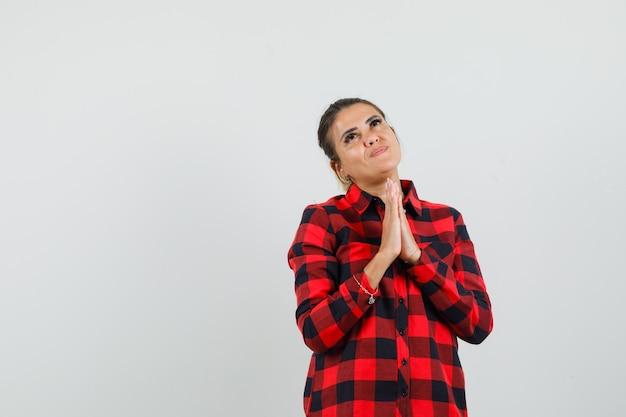 Młoda dama trzymając się za ręce w geście modlitwy w kraciastej koszuli i patrząc z nadzieją
