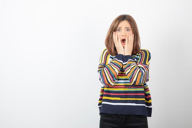 Młoda dama trzymając się za ręce w pobliżu policzków w swetrze i patrząc na kamery.