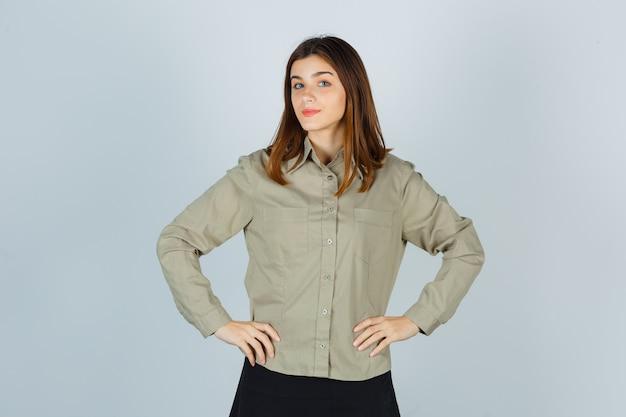 Młoda dama trzymając się za ręce w talii w koszuli, spódnicy i patrząc pewnie, widok z przodu.