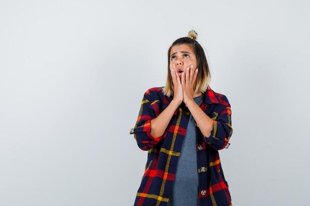 Młoda dama trzymająca dłonie przy ustach w casualowej koszuli w kratę i patrząca w szoku, widok z przodu.