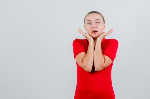 Młoda dama trzymająca dłonie w pobliżu brody w czerwonej koszulce i wyglądająca na rozbawioną