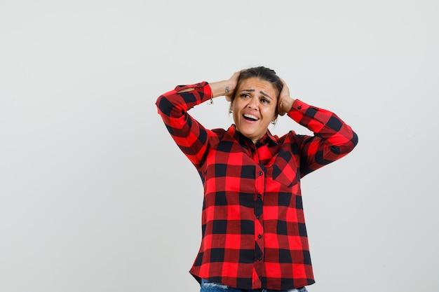 Młoda dama trzymająca głowę w rękach w kraciastej koszuli i wyglądająca na podekscytowaną.