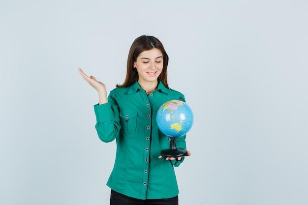 Młoda dama trzymająca kulę ziemską, rozkładająca dłoń w koszuli i wyglądająca wesoło. przedni widok.