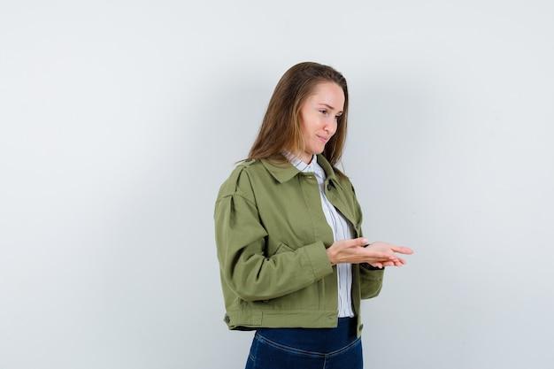 Młoda dama trzymająca otwarte dłonie w koszuli, kurtce i wyglądająca na delikatną, widok z przodu.