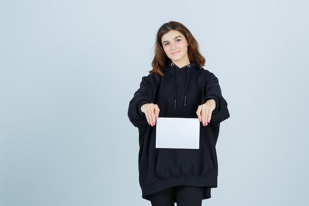 Młoda dama trzymająca papier przed sobą w obszernej bluzie z kapturem, spodniach i wyglądająca elegancko. przedni widok.