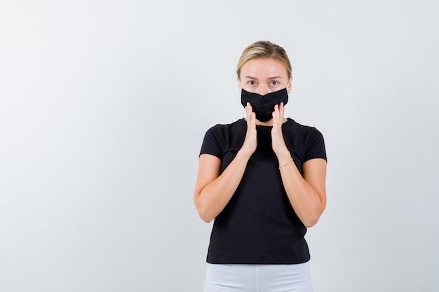 Młoda dama trzymająca ręce przy ustach w czarnej koszulce, masce i wyglądająca rozsądnie. przedni widok.