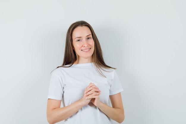 Młoda dama trzymająca ręce splecione w białej koszulce i wyglądająca pięknie