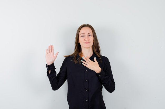 Młoda dama trzymająca rękę na klatce piersiowej i pokazująca dłoń
