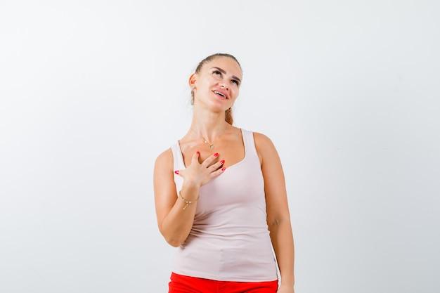 Młoda dama trzymająca rękę na piersi w beżowym bezrękawniku i wyglądająca radośnie, widok z przodu.