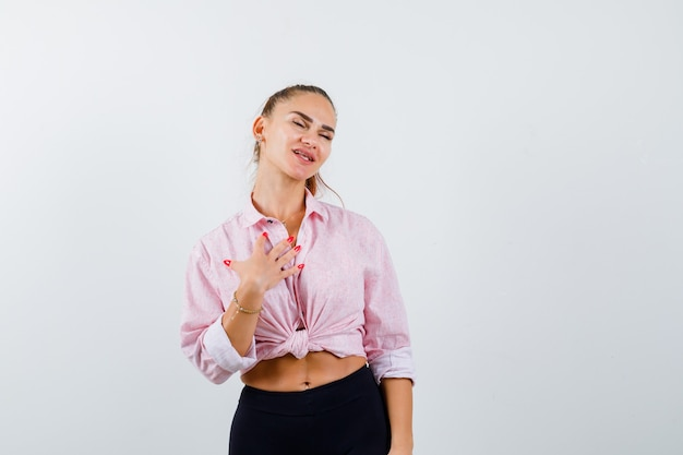 Młoda dama trzymająca rękę na piersi w koszuli, spodniach i wyglądająca na wdzięczną. przedni widok.