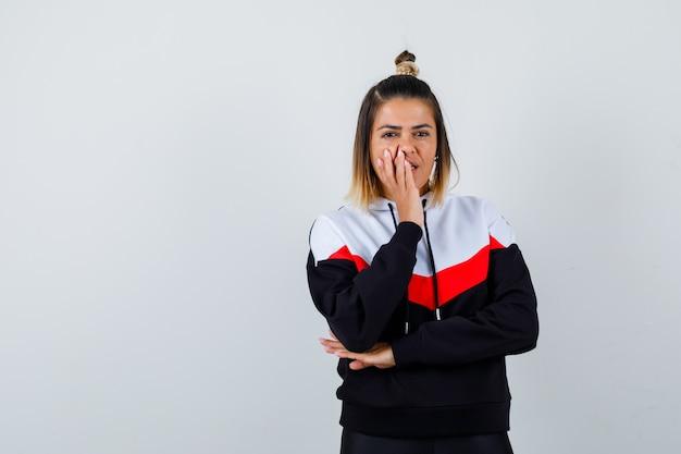 Młoda dama trzymająca rękę na ustach w swetrze z kapturem i wyglądająca na zadowoloną