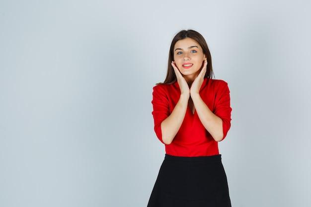 Młoda dama trzymająca rękę pod brodą w czerwonej bluzce, spódnicy i wyglądającej wesoło