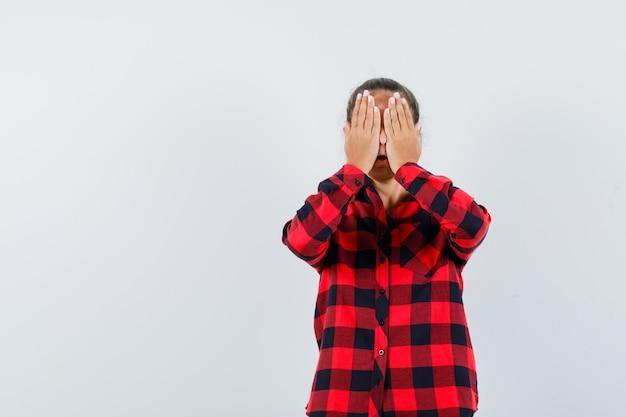 Młoda dama trzymająca się za oczy w koszuli w kratkę i wyglądająca na podekscytowaną