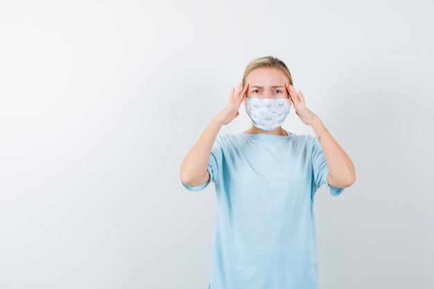 Młoda dama trzymająca się za ręce, aby wyraźnie widzieć w koszulce, masce i patrząc uważnie