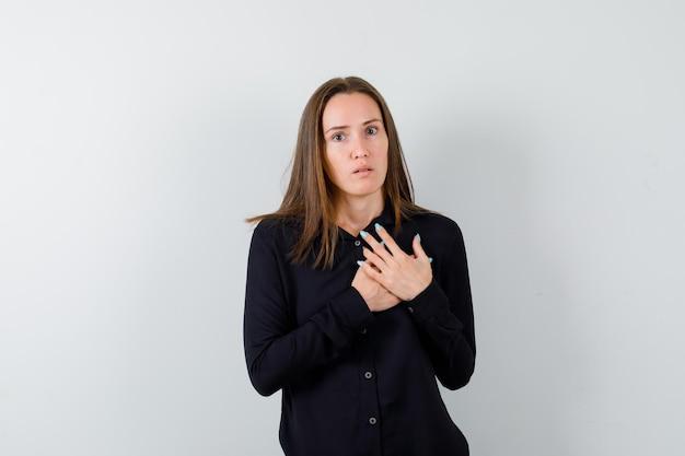 Młoda dama trzymająca się za ręce na klatce piersiowej i wyglądająca na przestraszoną
