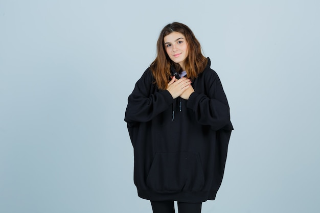 Młoda dama trzymająca się za ręce na piersi w dużej bluzie z kapturem, spodniach i wyglądająca na pełni nadziei. przedni widok.