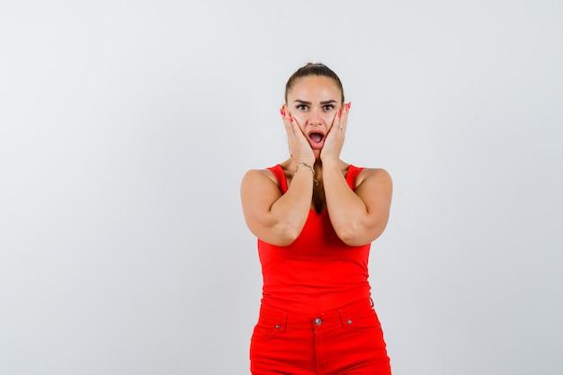 Młoda dama trzymająca się za ręce na policzkach w czerwonym podkoszulku, czerwonych spodniach i zdziwiona, widok z przodu.
