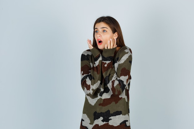 Młoda dama trzymająca się za ręce w pobliżu twarzy w swetrze, spódnicy i wyglądająca na zdziwioną