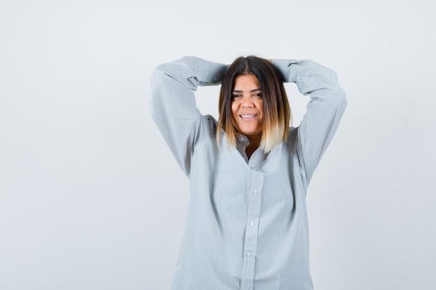 Młoda dama trzymająca splecione palce za głową w oversize'owej koszuli i wyglądająca na zadowoloną, widok z przodu.