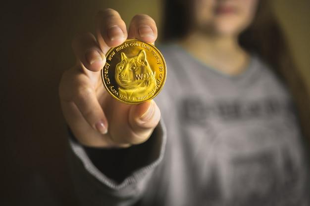 Młoda dama trzymająca w dłoni kryptowalutę dogecoin, widok zbliżenia