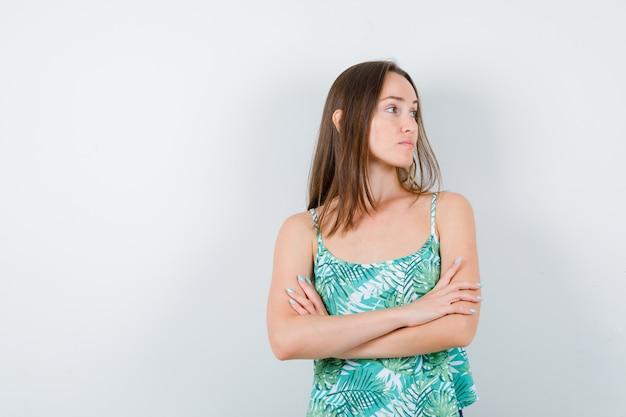 Młoda dama trzymająca założone ręce, patrząc na bok i patrząc skupiona, widok z przodu.