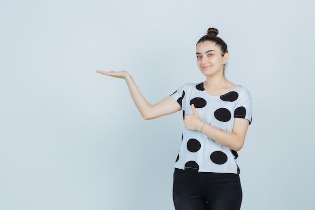 Młoda dama udająca, że coś pokazuje, pokazując kciuk w koszulce, dżinsach i wyglądająca na pewną siebie. przedni widok.