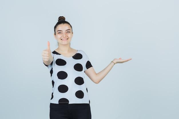 Młoda dama udająca, że coś pokazuje, pokazując kciuk w koszulce, dżinsach i wyglądająca na szczęśliwą, widok z przodu.