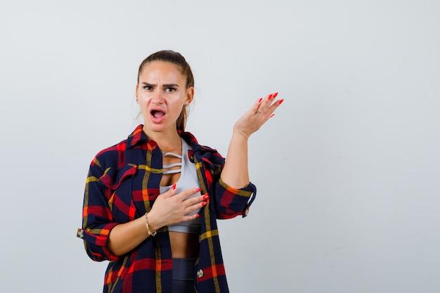 Młoda dama udaje, że coś pokazuje w koszuli w kratę i wygląda na zakłopotaną, widok z przodu.