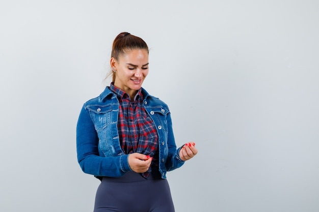 Młoda dama udaje, że trzyma coś, patrząc w dół w koszulę, kurtkę i patrząc wesoło, widok z przodu.