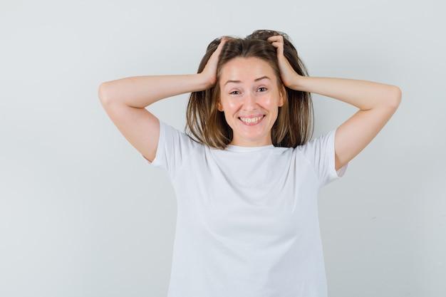 Młoda dama układa włosy rękami w białym t-shircie i wygląda ponętnie