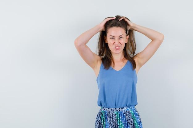 Młoda dama układa włosy w podkoszulek, spódnicę i wygląda ponętnie
