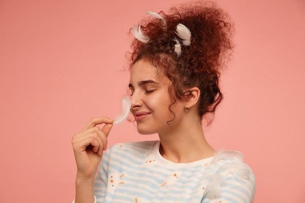 Młoda dama, urocza kobieta z rudymi kręconymi włosami. ubrana w pasiasty sweter z króliczkami i pokryta piórami, dotykająca piórem nosa. stań na białym tle, zbliżenie na pastelowo różowej ścianie